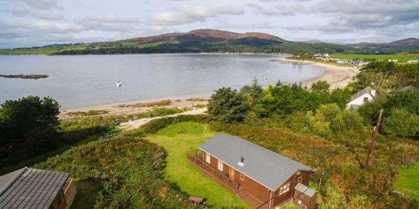 Panoramic view of the sea at Sandgreen with a timber lodge pitch in the foreground